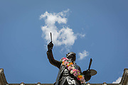 As a visual pun, the statue of Sir Joshua Reynolds seeminly paints clouds in blue sky from outside the Royal Academy in Piccadilly during the Summer Exhibition, on 13th August 2019, in London, England. This is a new cast of the original that was first exhibited outside the RA in 1904 and is an allegory of the human need for new challenges, of our instinct to always be scanning the horizon and the future. Sir Joshuas statue stands in the Annenberg Courtyard of Burlington House.