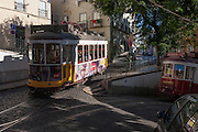 Tram lines merge on a narrow cobbled street shared by cars in Lisbon, Portugal.