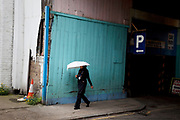 Woman with an umbrella walks past a car parking sign under some railway arches in the East End of London.