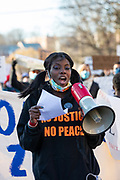 Yum-Yum Abdul uses a bullhorn to lead chants during a march remembering her friend Osaze Osagie who was killed by police in 2019.