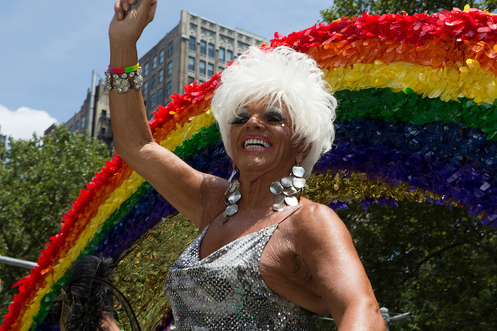 Framed by a rainbow, a participant in a sequined dress rides down 5th Avenue on a float.