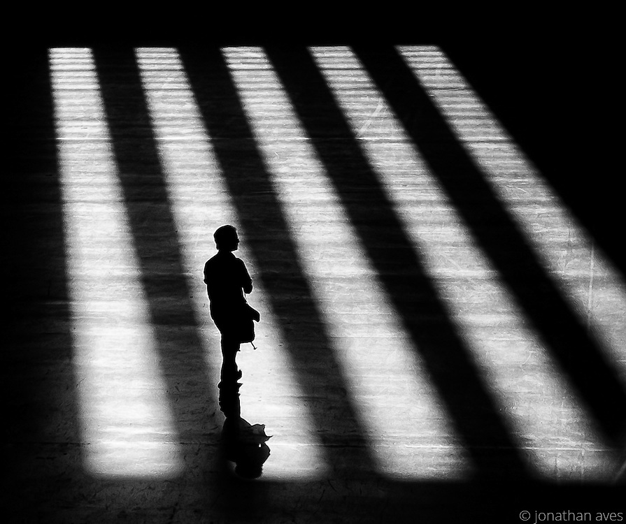 A lone man waiting in the Turbine Hall of the Tate Modern Art Gallery, London, UK.