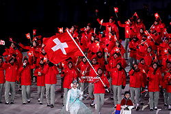 Switzerland flag bearer Dario Cologna leads out his team during the Opening Ceremony of the PyeongChang 2018 Winter Olympic Games at the PyeongChang Olympic Stadium in South Korea. PRESS ASSOCIATION Photo. Picture date: Friday February 9, 2018. See PA story OLYMPICS Ceremony. Photo credit should read: Mike Egerton/PA Wire. RESTRICTIONS: Editorial use only. No commercial use.