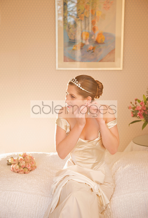 Bride in a white wedding gown sitting on a bed adjusting her earrings