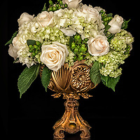 Bouquet of flowers in an old vase with a black background.