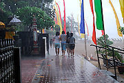 Four local girls walking in torrential rain storm. Sanur Beach, Bali, Indonesia.