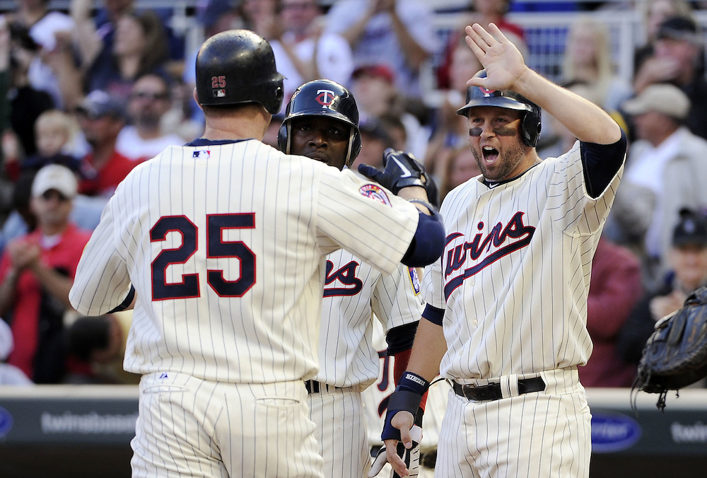 MINNEAPOLIS - SEPTEMBER 04:  Jim Thome #25 is greeted by Michael Cuddyer #5 of the Minnesota Twins after Thome hit his second home run of the game in the fourth inning against the Texas Rangers on September 4, 2010 at Target Field in Minneapolis, Minnesota.  The Twins defeated the Rangers 12-4.  (Photo by Ron Vesely)