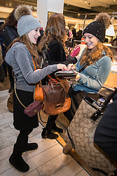 © Licensed to London News Pictures . 26/12/2013 . Manchester , UK . Women with multiple handbags in Selfridges quickly clear shelves of reduced products . Queues for Selfridges in Manchester , ahead of an 8am opening . Thousands of shoppers queue for hours in freezing temperatures in Manchester this Boxing Day morning (26th December 2013) in order to be amongst the first to purchase reduced price products in shops' sales . Photo credit : Joel Goodman/LNP