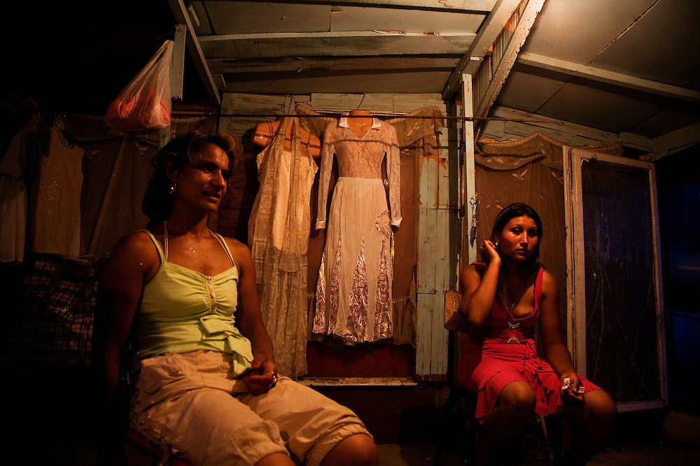 Women get ready for the evening celebration of a baptism in the Nova Gazela camp, with a fancy dress hanging on the wall.
