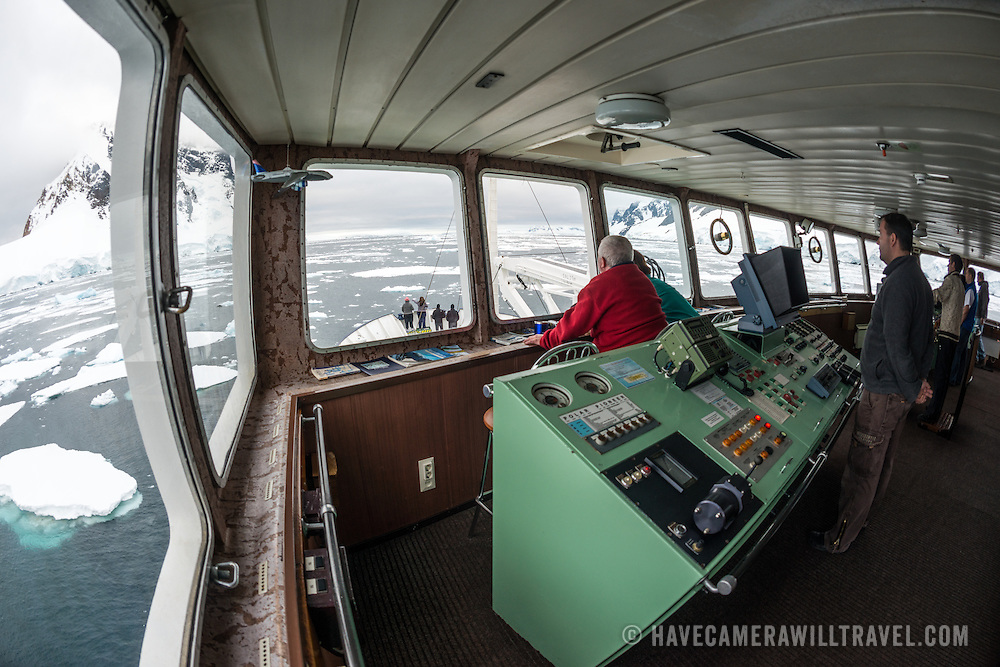 Wide-angle shot of a ship's bridge navigating the narrow Lemaire Channel in Antarctica. The bridge is on the Russian ship the Polar Pioneer, operated by Aurora Expeditions for Antarctic tourism.