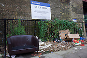 Fly-tipping left on a Lewisham street beneath a council sign threatening fines ad/or imprisonment.
