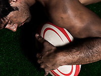 one caucasian sexy topless man portrait hugging a rugby ball on studio black background
