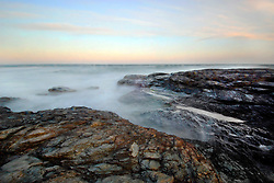The coastline along Newport's Ocean Drive is made of rocky granite and shale, onto which the North Atlantic waves crash and smooth the jagged edges. A pastel sky and long exposure soften the harsh winter New England coastline scene.