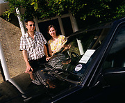 Ordinary husband and wife Mark and Christine Easterfield stand awkwardly with their Volvo car outside their large home near Cambridge, England. They are among the thousands of people who have each paid the $200,000 fare for seats on Richard Branson's Virgin Galactic space flights. Aboard the re-usable space vehicle will be 6 passengers, each of whom will have paid $200,000 for the 40 minute flight to 360,000 feet (109.73km, or 68.18 miles) and to experience just 6 minutes of weighlessness.   Flights start around 2009/10 from a Mojave desert test facility but therafter, at the new Philippe Starck-designed SpacePort America, New Mexico, USA. a 27 square mile, $225 million headquarters and mission control facility near Las Cruces.