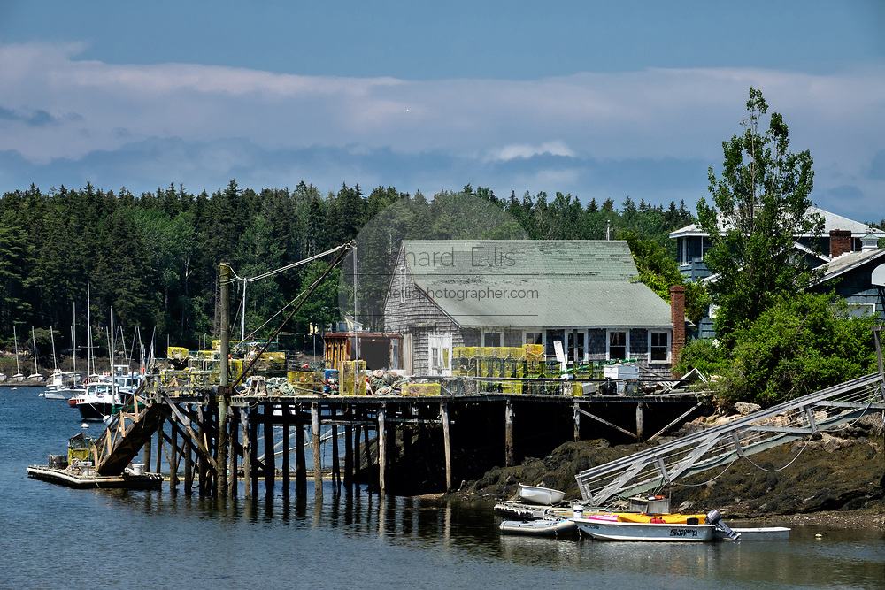 A lobster wharf piled with traps and fishing gear in the tiny village of Cozy Harbor in Southport, Boothbay, Maine.