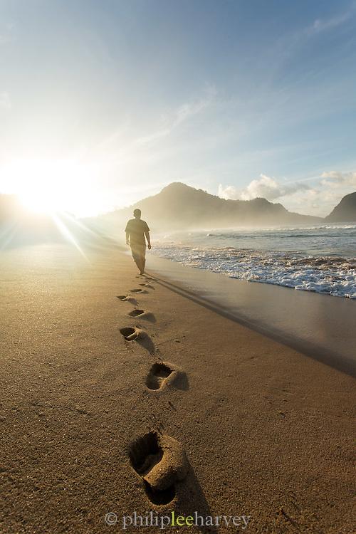 Man walking through the sand at sunset, Red Island Beach, Red Island, Banyuwangi Regency, East Java, Indonesia, Southeast Asia