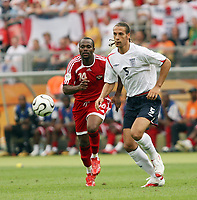 Photo: Chris Ratcliffe.<br /> England v Trinidad & Tobago. Group B, FIFA World Cup 2006. 15/06/2006.<br /> Rio Ferdinand from England clashes with Stern John from T&T.
