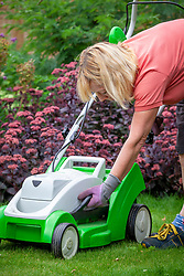 Raising the height of lawnmower blades before cutting a lawn during a dry spell