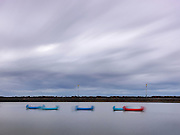 Limited Editions of 17<br /> Canoes float tethered in evening breeze in a tidal pond on the English Coast at Saint Annes near Blackpool