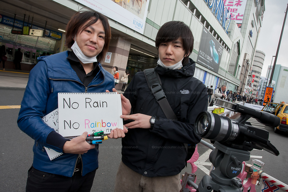 Kakagu Komazaki (left) and Yoshihito Oshima (right) ask passersby to write and record messages on video to send to the people of Fukushima after a magnitude 9 earthquake and large tsunami hit the Tohoku region of north east Japan  on March 11th killing nearly 20,000 people and causing massive destruction along the whole coast, and a melt-down at the Fukushima Daichi nuclear power station. Shinjuku, Tokyo, Japan March 16th 2011