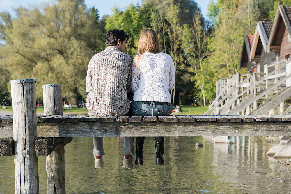 Couple sitting wooden jetty lake tranquil