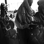 Made Manur (centre) takes his children and two wives, Abdiya Ahmed (left) and Fatima Aden Mohammed (right) and his 10 children to the medical check up after the registration process in Dagahaley refugee camp in the Dadaab, in northeastern Kenya. His other 2 year old daughter, Habiba died along the way to the camp. Hundreds of thousands of refugees are fleeing lands in Somalia due to severe drought and arriving in what has become the world's largest refugee camp. Photo: Sanjit Das/Panos