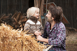 Father and son playing in farm, Bavaria, Germany
