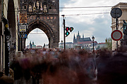 """Huge amounts of mostly visitors   moving across a traffic light to the beginning of Charles Bridge and towards """"Lesser Town"""" (Mala Strana) and Prague Castle."""