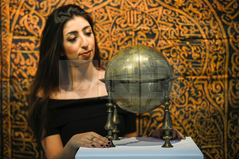 """© Licensed to London News Pictures. 18/10/2019. LONDON, UK. A staff member poses with a """"Safavid brass celestial globe and frame"""", Persia, 17th century (Est. GBP80,000-120,000).  Preview of Islamic, Indian and Middle Eastern art to be auctioned at Sotheby's, New Bond Street, on 22 and 23 October.  Photo credit: Stephen Chung/LNP"""