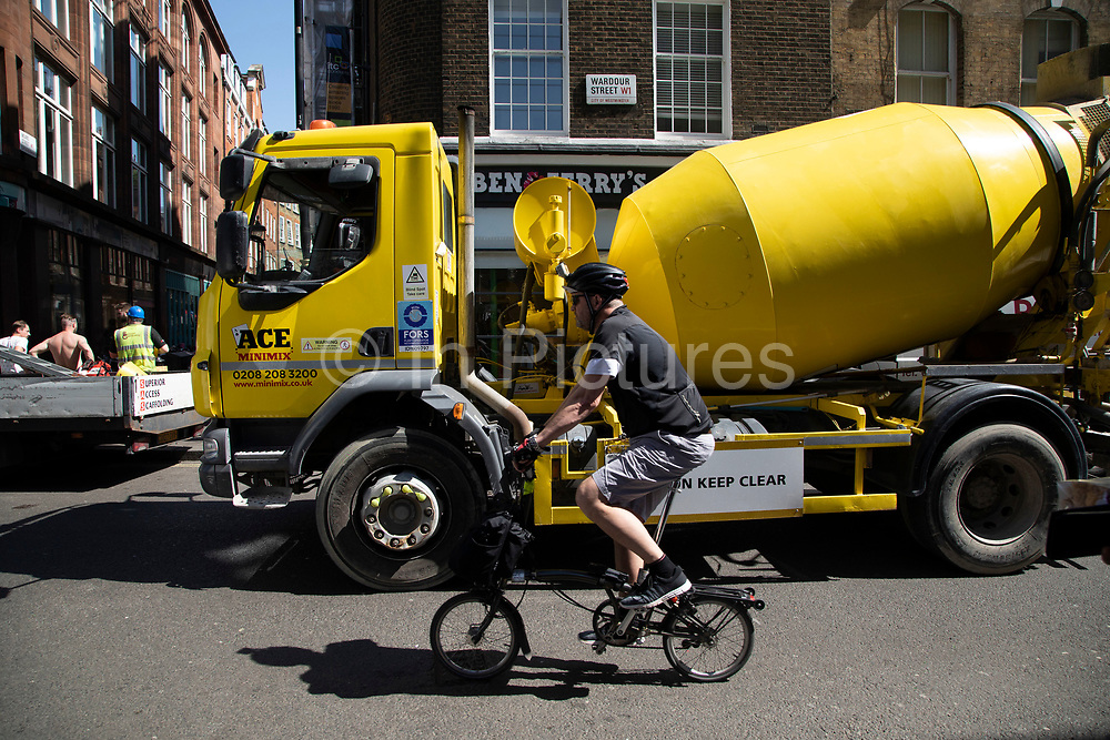 Busy street scene on Wardour Street in Soho as vehicles and pedertrians pass at the the same time including a yellow concrete mixer in London, England, United Kingdom. A man on a Brompton foldable bike passes.