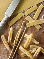 Traditional Italaian Casarecce pasta being made and shaped in a rustic setting