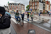 Een fietser kruist op het Muntplein in Amsterdam voetgangers terwijl hij op zijn telefoon kijkt.<br /> <br /> A cyclists crosses pedestrians at the Munt Square while looking on his phone.