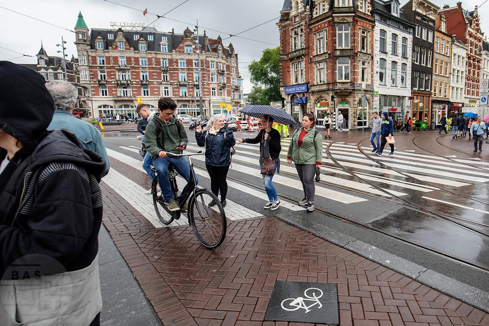 Een fietser kruist op het Muntplein in Amsterdam voetgangers terwijl hij op zijn telefoon kijkt.<br /> <br /> A cyclists crosses pedestrians at the Munt Square while looking on his phone.