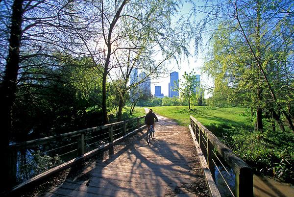 Stock photo of a girl riding her bicycle across a wooden bridge in Buffalo Bayou Park