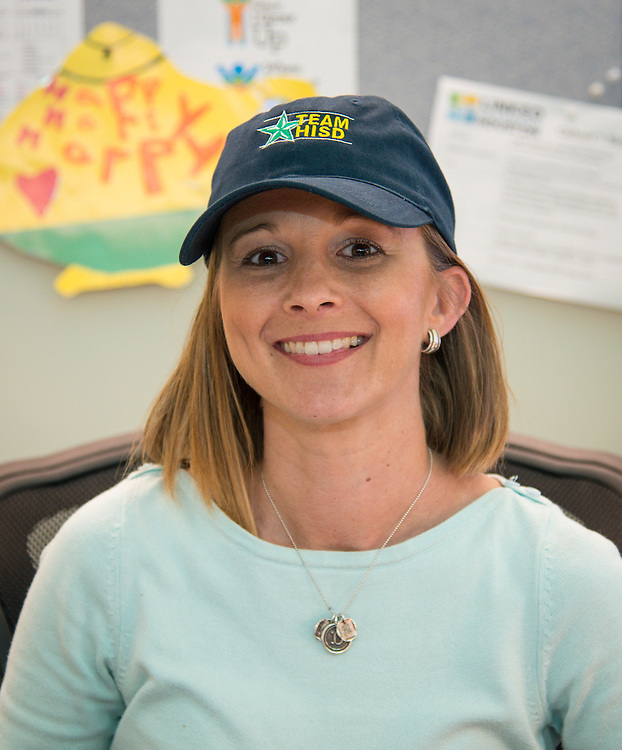 Dana Sturdevant wears a Team HISD cap after she was recognized during a Central Office staff meeting, April 8, 2014.