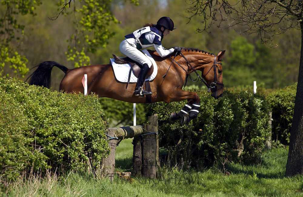 Young woman rides a dark bay horse in a cross-country eventing competition, Gloucestershire, United Kingdom