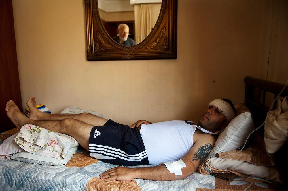 Alawite district Jabal Mohsen. Chaban Mahmoud was wounded in an attack in the street, where he was hit on the head with a stick. He is the father of four children. His uncle is visible in the mirror...Quartier alaouite Jabal Mohsen. Mahmoud Chaban a été  blessé lors d'une attaque dans la rue, il a été frappé à la tête avec un bâton. Il est père de 4 enfants. Son oncle est visible dans le miroir.