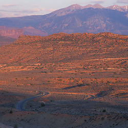 Arches National Park, UT..The Park Road winds through the Utah Desert.  La Sal Mountains are in the distance.