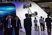 Visitors walk past a vehicle chasis display at the Beijing International Automotive Exhibition in Beijing, China, on Monday, April 25, 2016. China is leading the way to move towards new energy vehicles especially electrification as it sees an opportunity to leap frog traditional powerhouses in the automobile industry.