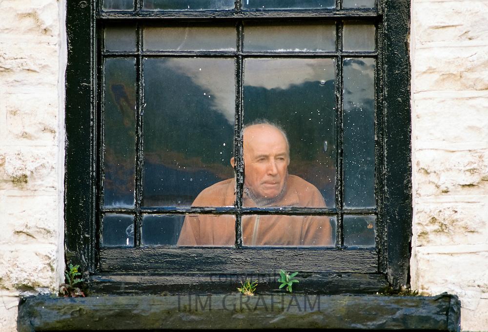 Elderly man alone at a window, UK
