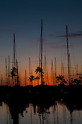 A beautiful sunset with the masts of sailboats silhouetted.