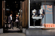 A security guard inspects a customer's bag at the entrance of menswear retailer Auston Reed in central London.