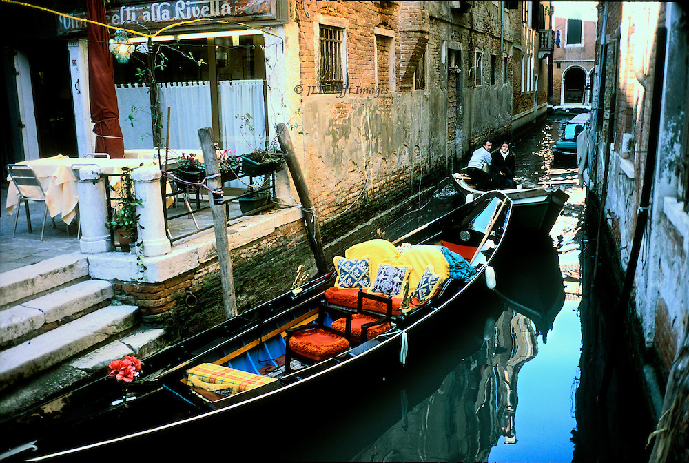 Young couple in a motor boat eases carefully past a gondola moored by a restaurant terrace in Venice.  The restaurant is deserted, though the gondola is elaborately fitted out for tourism.  But the couple in the motor boat have to go somewhere, in a justaposition of work and leisure.