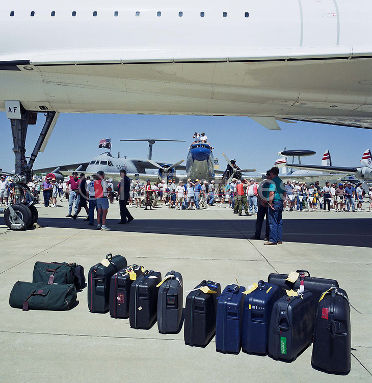 Baggage belonging to a British Airways Concorde crew is lined up beneath their aircraft after arriving at Oshkosh Air Venture, the world's largest air show in Wisconsin USA. Twelve cases match 12 of Concorde's tiny windows and some of the crowd either take shelter from the sun or walk around the supersonic jet in awe of this engineering marvel. Their baggage is lined up beneath the aircraft during its visit to this huge show in Wisconsin, USA. Close to a million populate the mass fly-in over the week, a pilgrimage worshipping all aspects of flight. The event annually generates $85 million in revenue over a 25 mile radius from Oshkosh. Picture from the 'Plane Pictures' project, a celebration of aviation aesthetics and flying culture, 100 years after the Wright brothers first 12 seconds/120 feet powered flight at Kitty Hawk,1903.