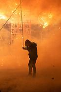 Un pirotécnico sostiene un tramo de mecha esperando el momento justo para encenderla.  /  A pyrotechnician holds a section of fuse waiting the right moment to light it up.