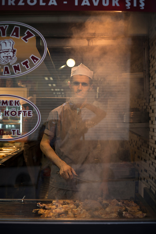 View from the sidewalk and through a window of a restaurant employee grilling meat in the Beyoğlu district of Istanbul, Turkey