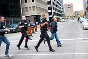 Police run through the streets of Ottawa while securing the downtown core during an active shooter situation following an attack on the War Memorial.