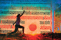 Happy woman leaping through the landscape with a Sanskrit sun. Woman demonstrating yoga poses and experiencing the spirit of joyfulness.