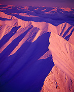 Aerial view of a winter sunrise illuminating the Arrigetch Peaks of the Brooks Range, Gates of the Arctic National Park, Alaska.