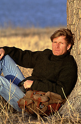 All American man leaning against a tree at sunset